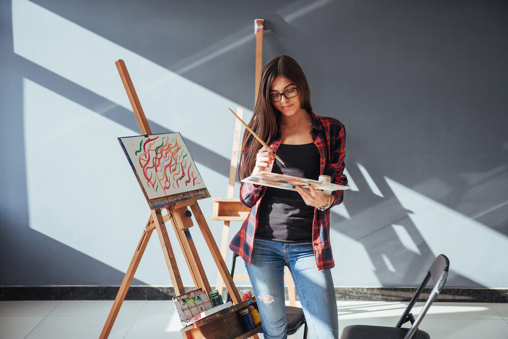 woman painting with easel