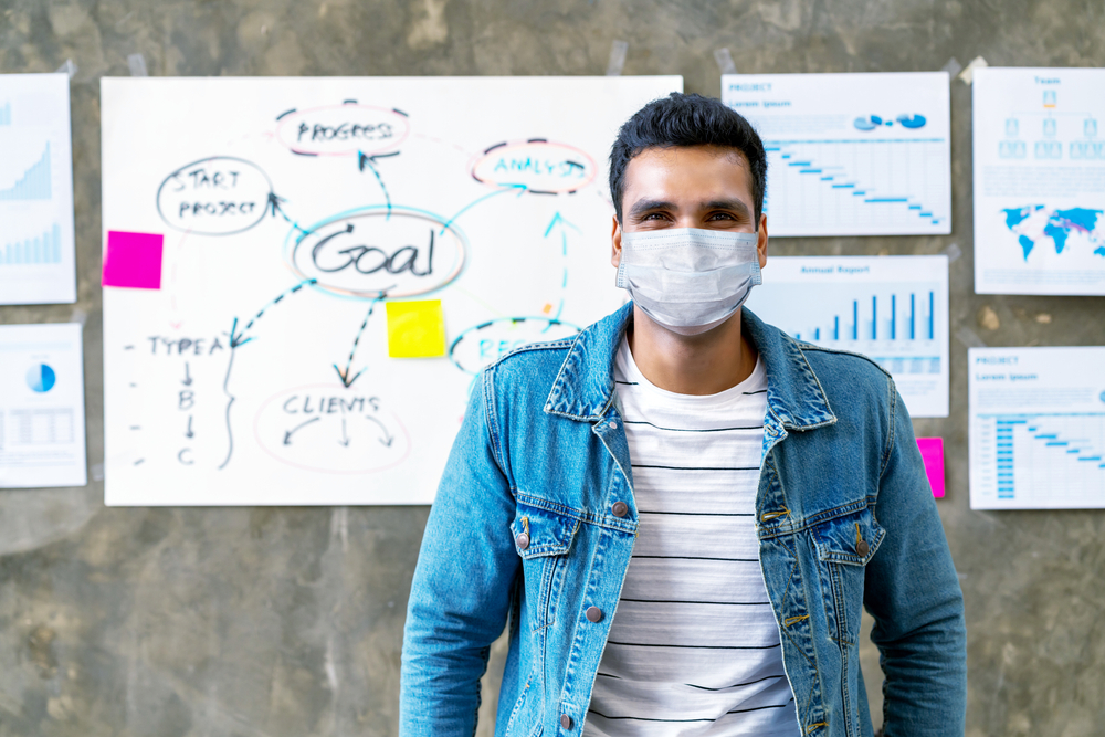 Portrait of young asian man worker wear medical mask protection looking at camera smiling under surgical mask in office workspace