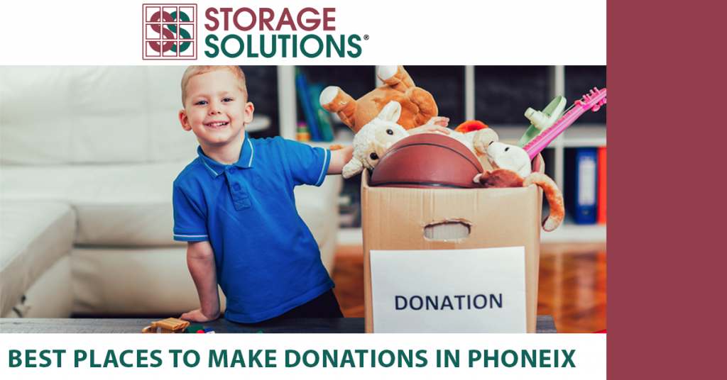 child next to box of toys and clothes for a donation center in phoenix